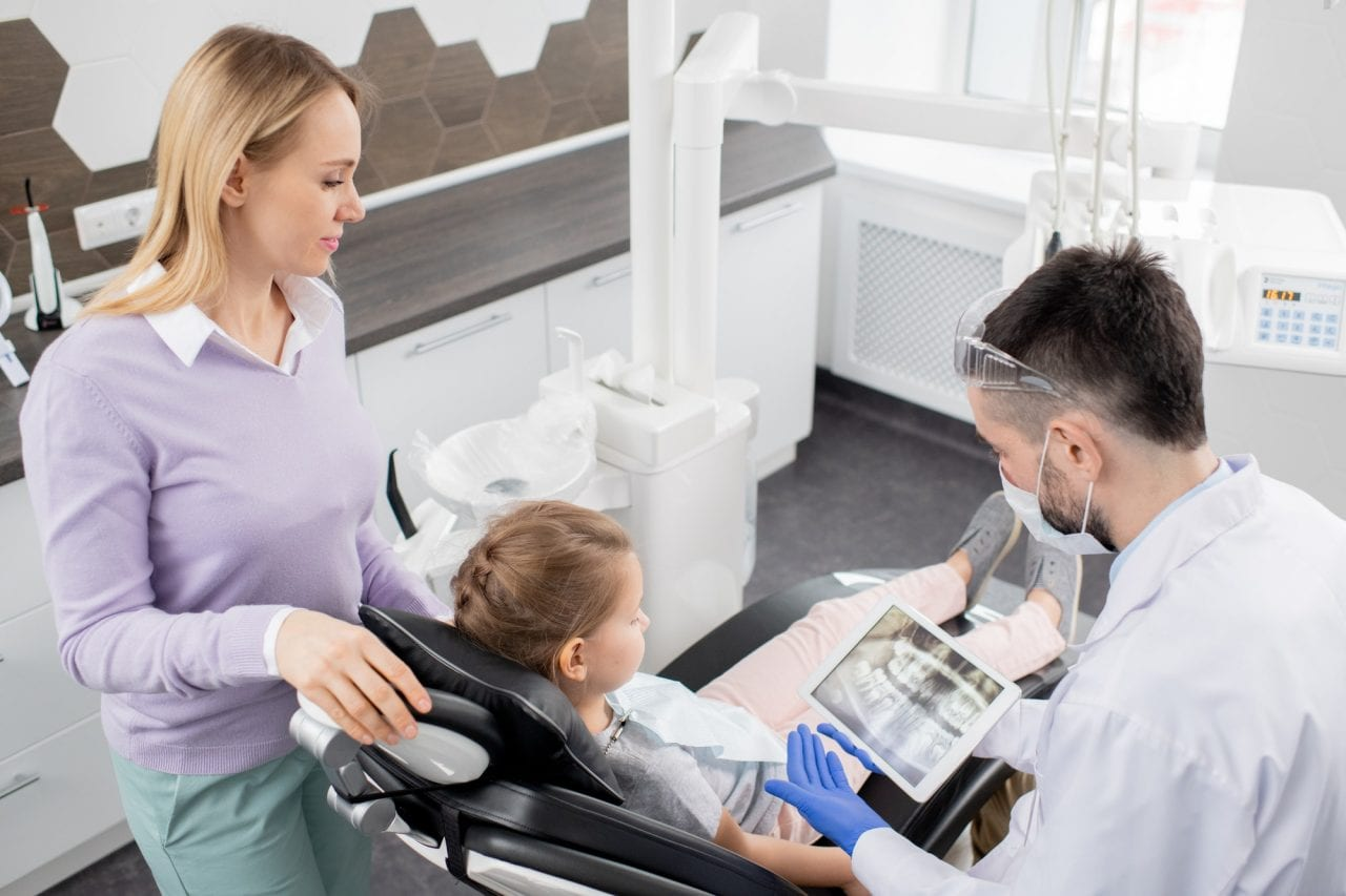 young-contemporary-dentist-showing-dental-x-ray-in-tablet-to-his-little-patient-1280x853.jpg
