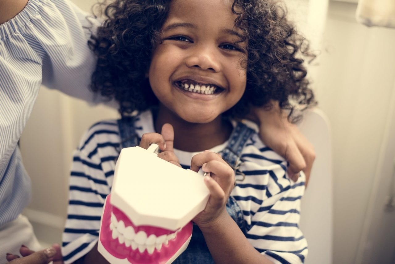 cheerful-young-kid-holding-a-dental-model-1280x854.jpg